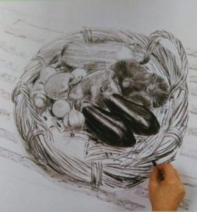 hand completeing a drawing of a basket with vegetables