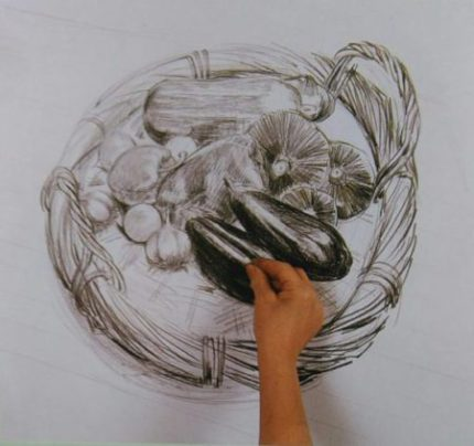 hand adding finishing touches to the drawing of a basket with vegetables