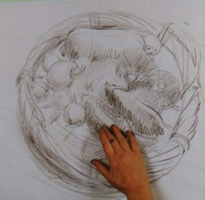 hand on a sketch of a basket with vegetables