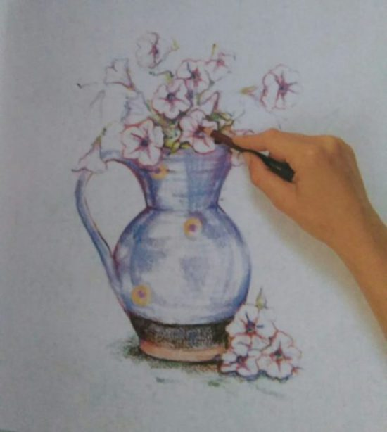 hand adding finishing details to a drawing of flowers in a jug made with colored pencils