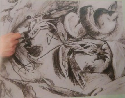 hand finishing the drawing of shrimp done with charcoal pencils