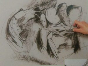 hand with eraser removing details from a sketch of srhrimps made with charcoal pencils