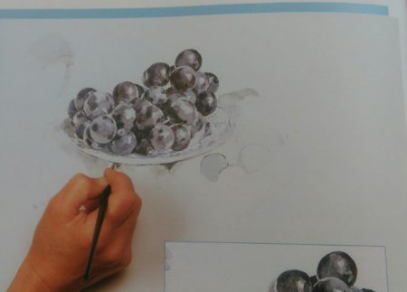 hand sketching black grapes on a plate with watercolors