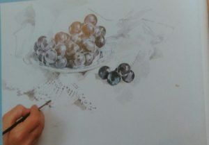 hand with a brush adding details to a watercolor painting of grapes