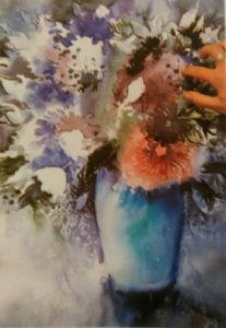 hande removing pait from a painting of flowers in a vase made with watercolors with wet on wet technique
