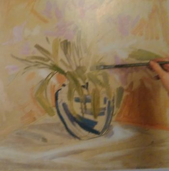 hand sketching flowers in a vase with paintbrush