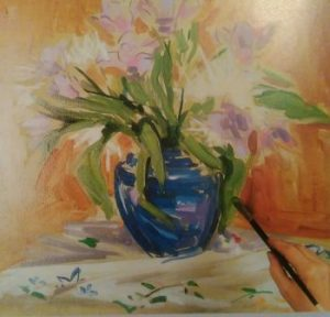 hand with paintbrush adding details to a painting of a vase with flowers