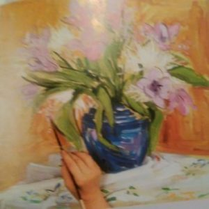 hand with a paintbrush finishing the painting of a blue vase with flowers using watercolors