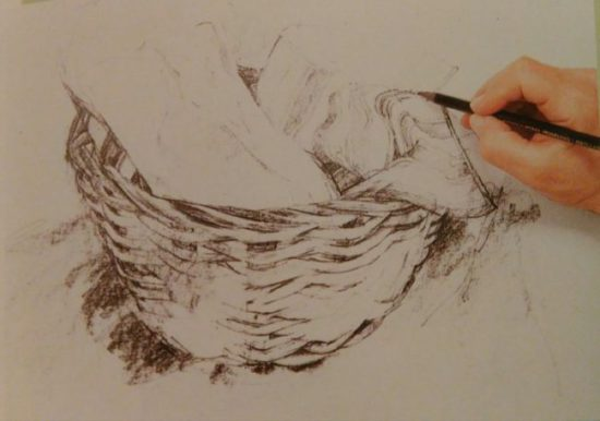 Hand with graphite sketching a basket with cloth