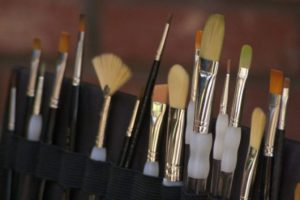 several different paintbrushes in a canvas brush holder
