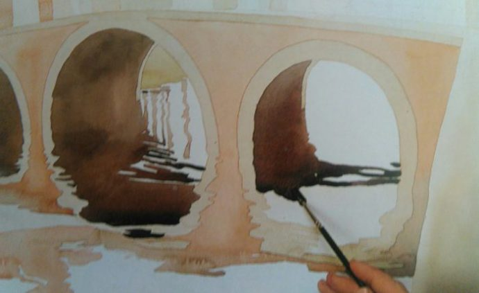 paitbrush adding details to a bridge on the water on a painting made with watercolors