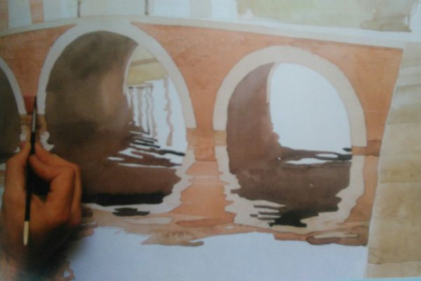 hand with a brush finishing the painting of a bridge with watercolorse