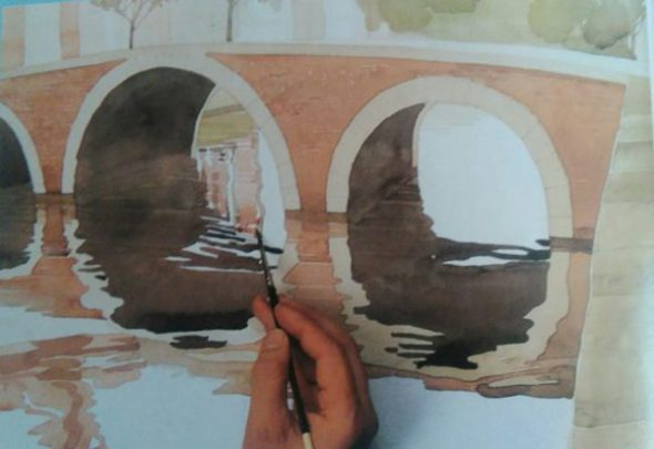 hand with the paintbrush adding finishing details to a painting of a bridge made with watercolors