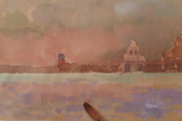 paintbrush on a sketch of a sunset made with watercolors