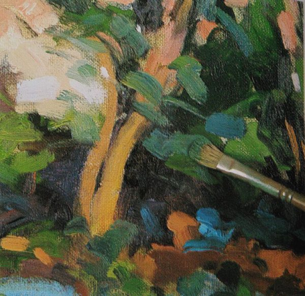 paintbrush adding details to a tree with oil colors