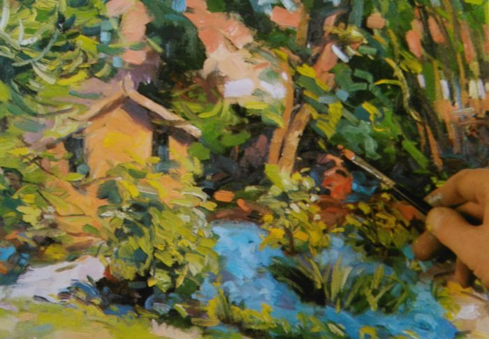 hand with a paintbrush adding details to an oil painting of a house and tress