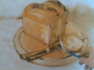 hand with a brushes addingfinal details to the painting of a bread and knife on a cutting board