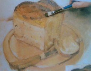 hand with a brush painting the bread on a cutting board