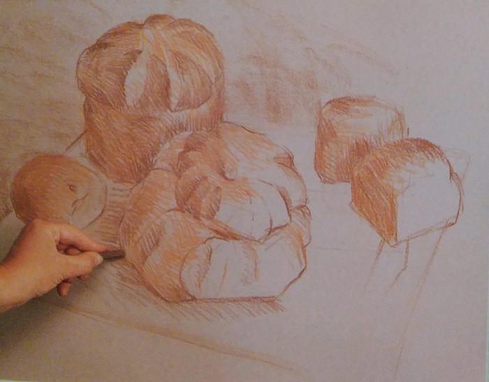 hand sketching several pastries with conte crayons