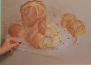 hand adding finishing details to the drawing of pastries made with conte crayons