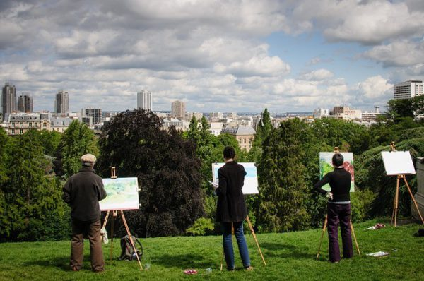 Several artist painting in front of portable easels on a hill
