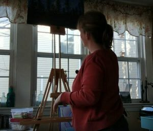 woman painting in front of mon marte field easel