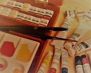 several diiferent watercolors and paintbrushes