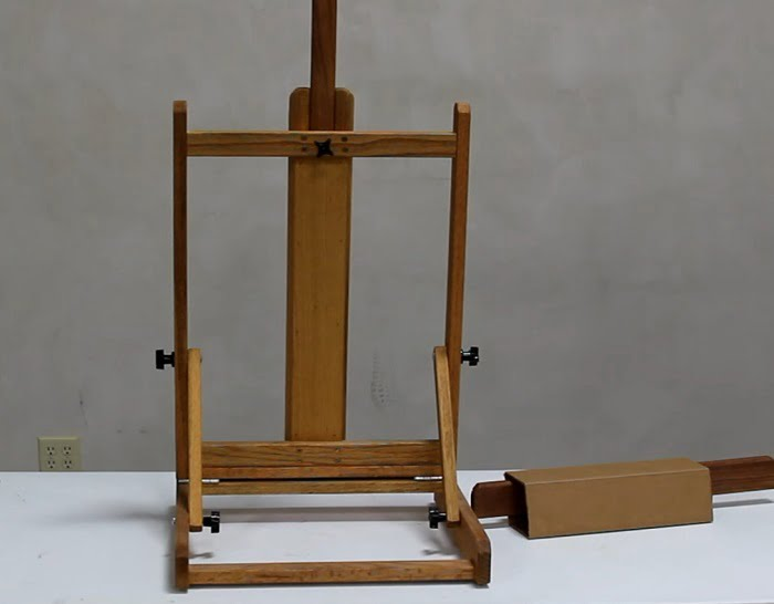 Best deluxe table top easel not fully assembled with a bottom canvas holder standing on the table next to if wrapped in cardboard