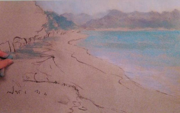 hand sketching a landscape with soft pastels