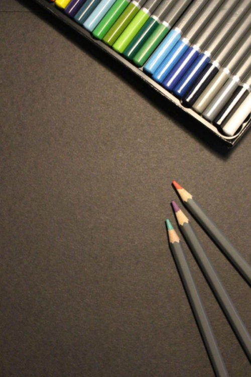 several pencils next to an open box of colored pencils on a brownish grey surface