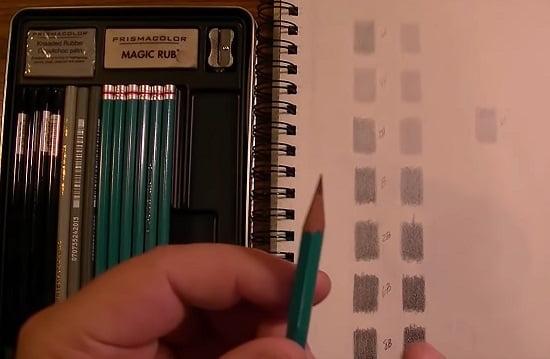 Tone chart of prismacolor premier graphite pencils next to the open box of pencils