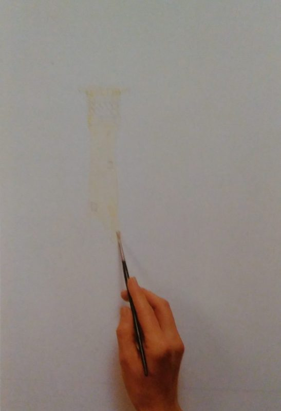 hand with a paintbrush starting to sketch a lighthouse on a white surface