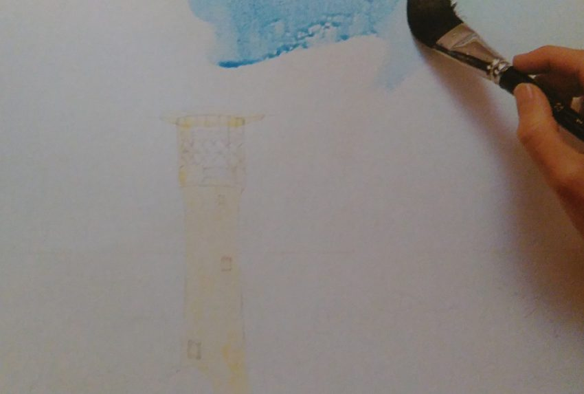 hand with a paintbrush painting a sketch of a lighthouse with watercolors